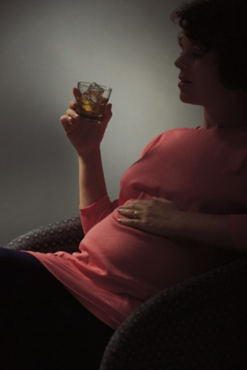 Pregnant woman drinking alcoholic beverage : Stock Photo