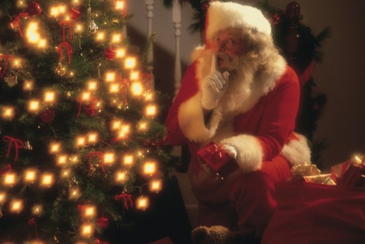 Stock Photo: 1557R-366644 Santa Claus placing presents under Christmas tree