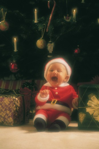 Baby in Santa Claus costume by Christmas tree : Stock Photo