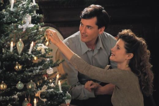 Stock Photo: 1557R-366750 Couple decorating Christmas tree