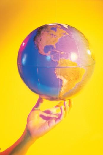 Stock Photo: 1557R-367342 Hand balancing globe showing western hemisphere