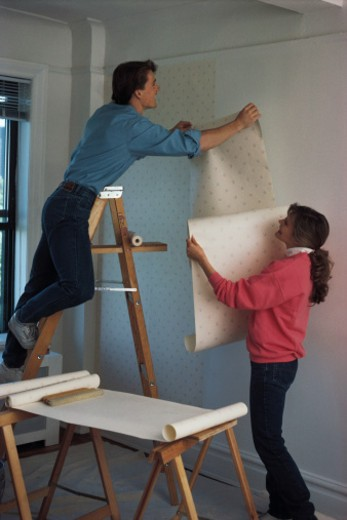 Couple wallpapering room : Stock Photo