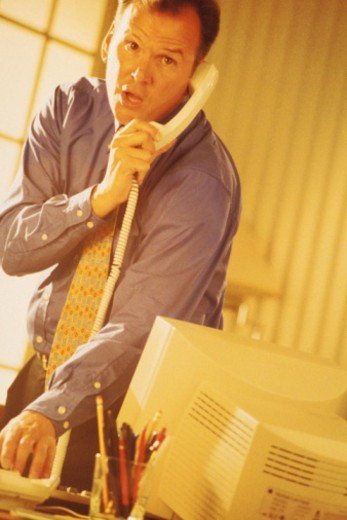 Businessman at desk talking on telephone : Stock Photo