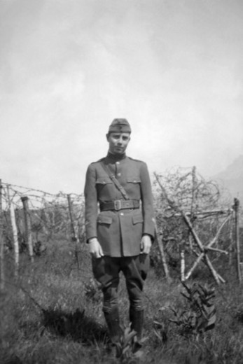 Vintage image of man in uniform near razor wire fence : Stock Photo