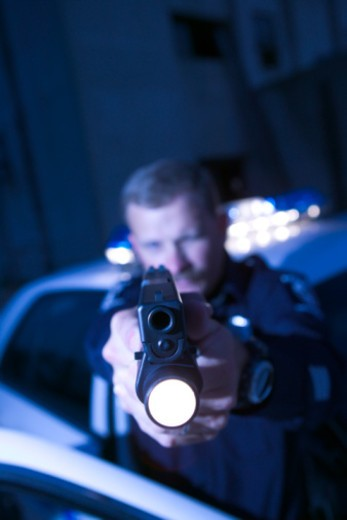 Police officer aiming gun : Stock Photo