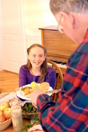 Stock Photo: 1557R-369788 Grandfather serving turkey to granddaughter