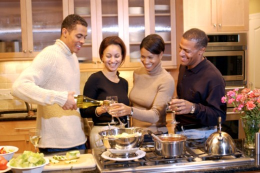 Couples toasting wine while cooking dinner : Stock Photo