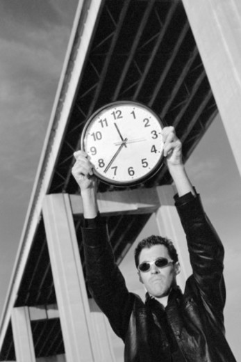 Man under bridge holding clock : Stock Photo