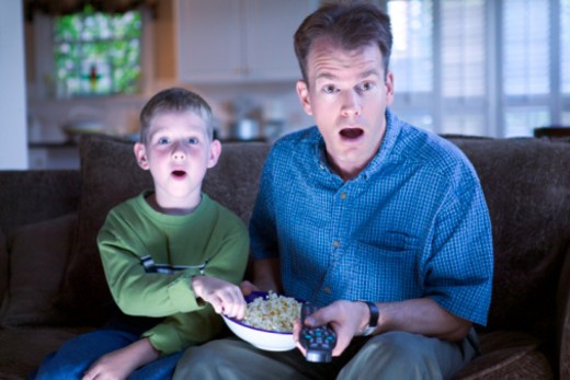 Father and son with remote control and popcorn : Stock Photo