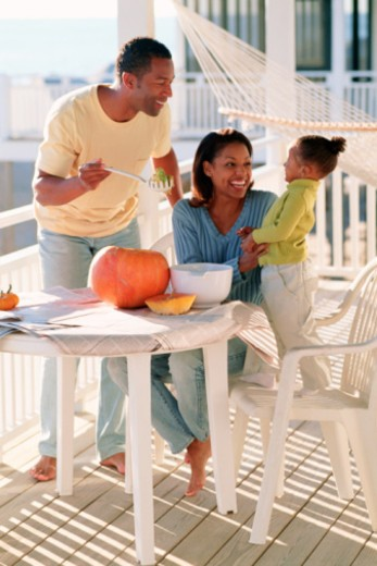 Family carving pumpkin on porch : Stock Photo