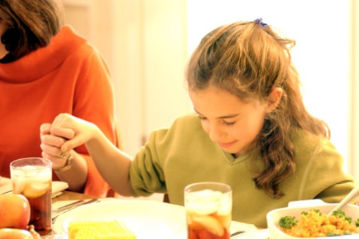 Girl with mother praying before meal : Stock Photo