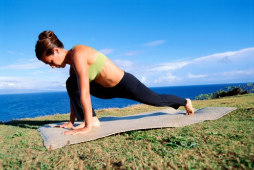 Woman doing yoga near coast : Stock Photo