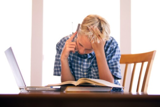 Stock Photo: 1557R-374923 Boy using cell phone and doing homework