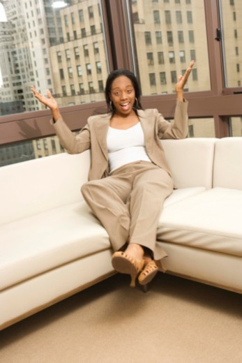 Stock Photo: 1557R-376640 Urban woman sitting on couch