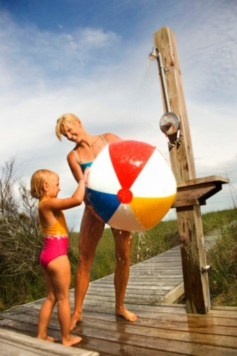 Mother and daughter washing beach ball at outdoor shower : Stock Photo