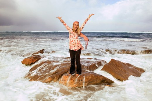 Stock Photo: 1557R-377301 Woman standing on rock in ocean