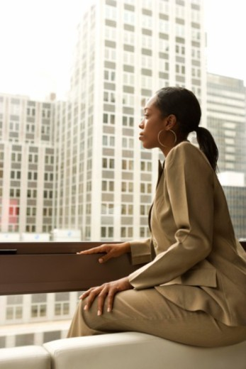 Businesswoman looking out window of high rise : Stock Photo