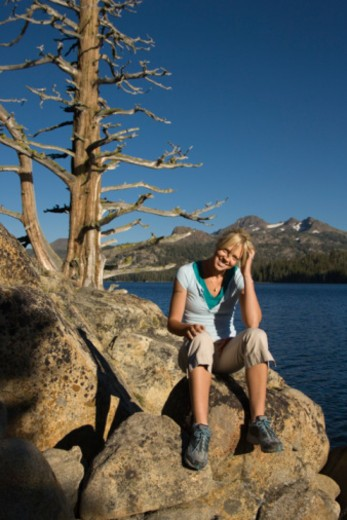 Stock Photo: 1557R-378935 Woman sitting on rock