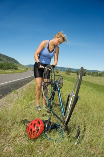Stock Photo: 1557R-379164 Woman fixing flat tire on bicycle