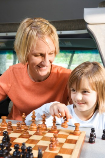 Mother and daughter playing chess : Stock Photo