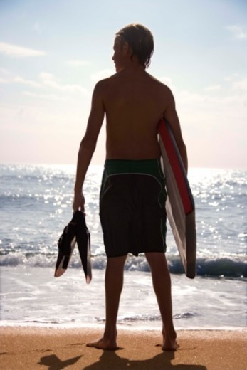 Silhouette of boy with boogie board and flippers : Stock Photo