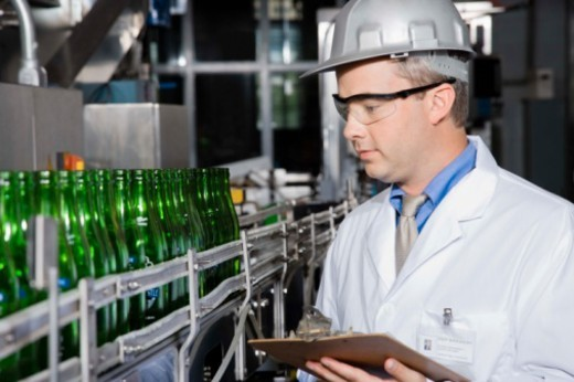 Stock Photo: 1557R-379910 Worker with clipboard by assembly line in brewery
