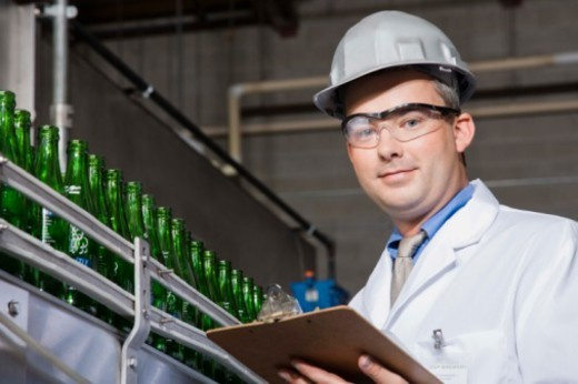 Stock Photo: 1557R-379919 Worker with clipboard by assembly line in brewery