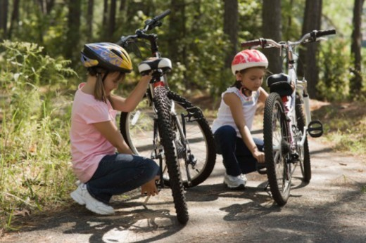 Stock Photo: 1557R-379945 Girls fixing bicycles outdoors