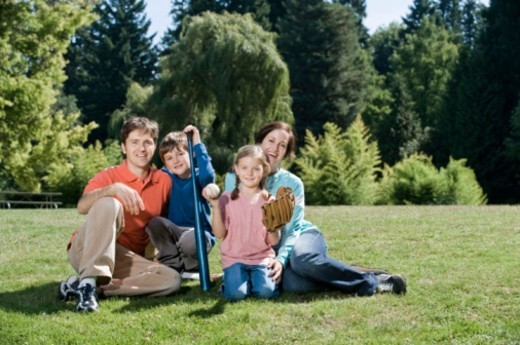 Smiling family with baseball equipment : Stock Photo
