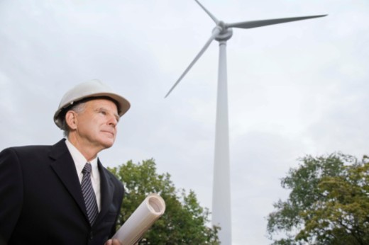 Stock Photo: 1557R-380564 Businessman in hardhat by a wind turbine