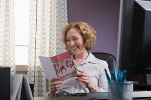 Woman reading a birthday card : Stock Photo