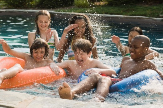 Children playing and splashing in swimming pool : Stock Photo