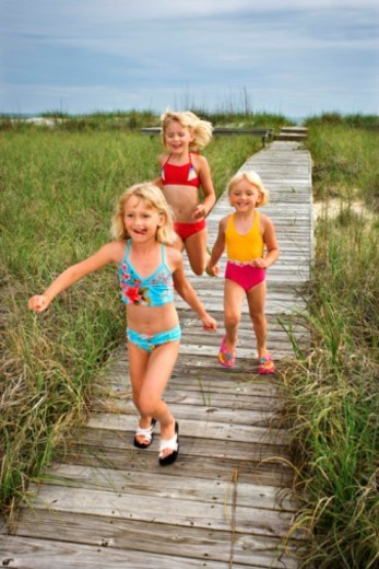 Girls running down boardwalk : Stock Photo