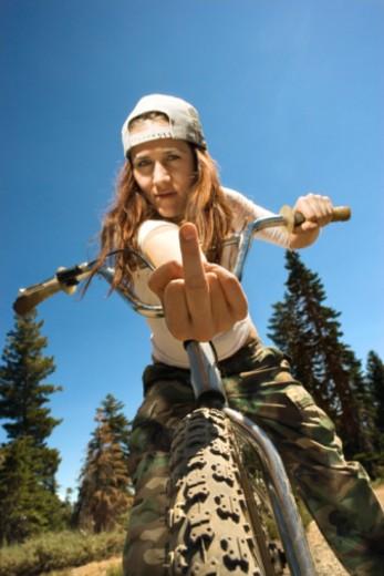 Woman on mountain bike making obscene gesture : Stock Photo