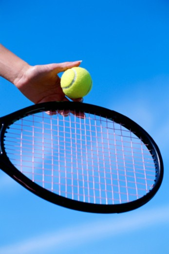 Hand with tennis ball and tennis racket : Stock Photo