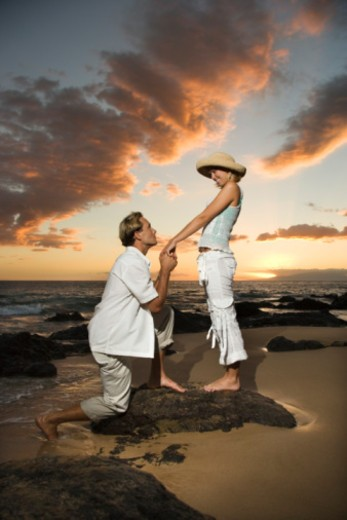 Stock Photo: 1557R-385249 Man proposing to woman on beach