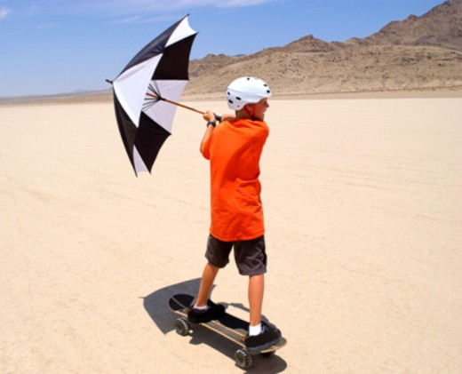 Stock Photo: 1557R-385283 Boy with umbrella and skateboard in desert