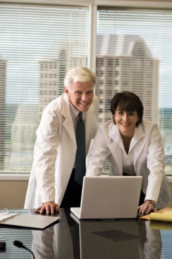 Doctors in lab coats looking at laptop computer : Stock Photo