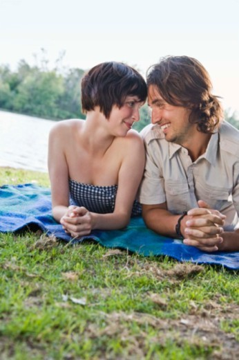 Couple lying down in grass : Stock Photo