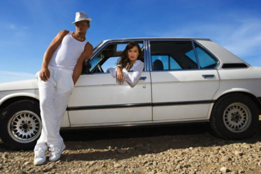 Man and woman posing by car : Stock Photo