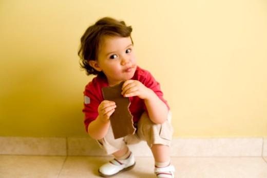 Boy eating chocolate bar : Stock Photo