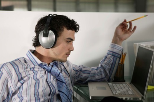 Businessman working at laptop while listening to music : Stock Photo