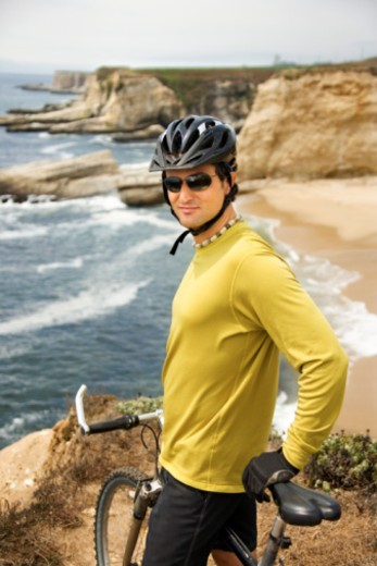 Man posing with bicycle by coast : Stock Photo