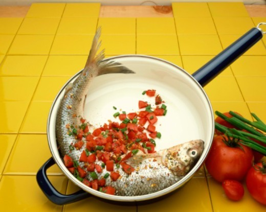 Fish in frying pan with salsa : Stock Photo