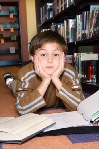 Stock Photo: 1557R-390597 Boy doing homework in library