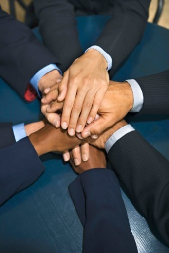 Businesspeople putting hands together : Stock Photo