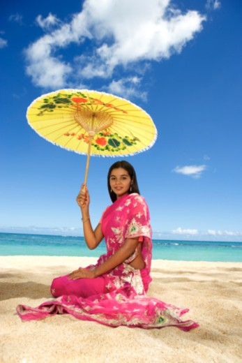 Teenage girl with parasol on beach : Stock Photo