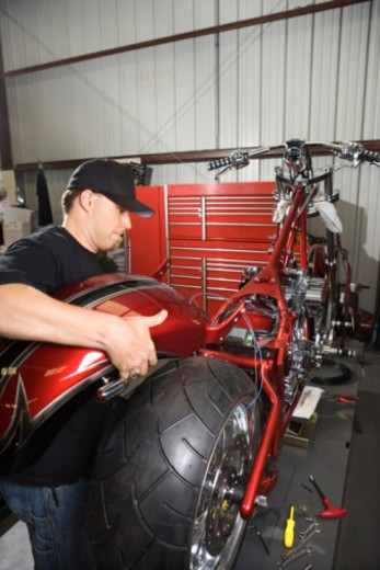 Stock Photo: 1557R-391384 Man assembling motorcycle