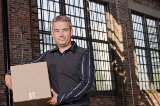 Man carrying box in warehouse : Stock Photo