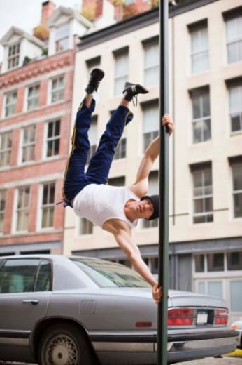 Man hanging on lamppost : Stock Photo